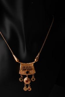 Goldene halskette mit isoliert auf schwarzer oberfläche