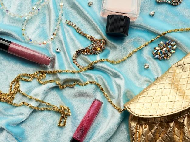 Goldene handtasche, lipgloss und perlen auf blauem grund