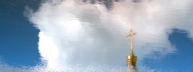 Goldene haube und orthodoxes kreuz reflektierten sich in der wasseroberfläche