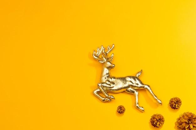 Goldene hirsche und tannenzapfen auf gelb