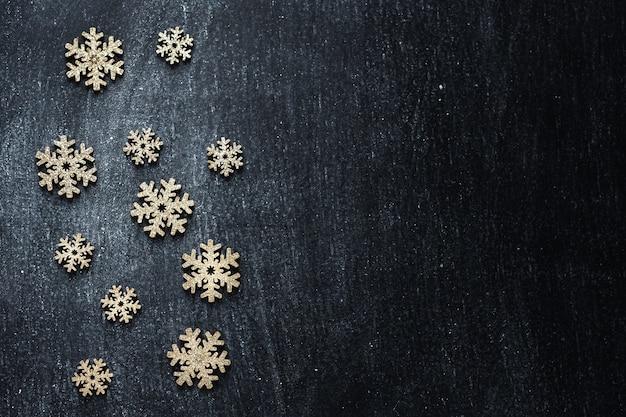 Goldene hölzerne schneeflocken auf schwarzer tafel. flache lage.