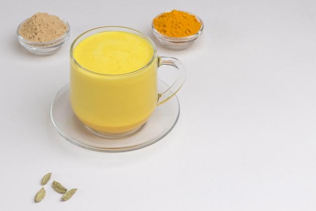Goldene indische kurkuma-milch im glas mit zutaten zum kochen