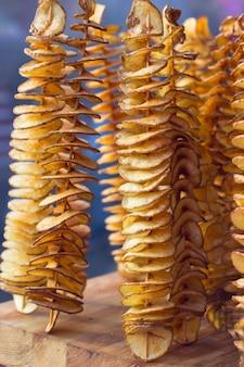 Goldene kartoffelchips auf einem dünnen holzstab.