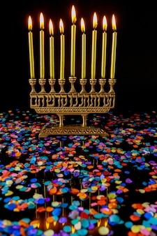 Goldene kerzen auf menora und konfetti auf schwarzem hintergrund. jüdisches feiertags-chanukka-symbol.