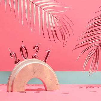 Goldene kerzen mit dem neuen jahr 2021 auf dem marmorbogen, palmblätter, konfetti auf gelbem hintergrund mit dem horizont. festliches trendstillleben.
