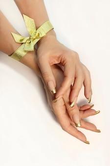 Goldene klassische französische maniküre mit einer schleife an der hand