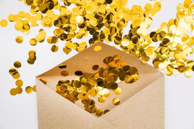 Goldene konfetti im papierumschlag
