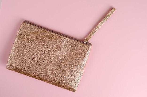 Goldene kosmetiktasche auf pastellrosa