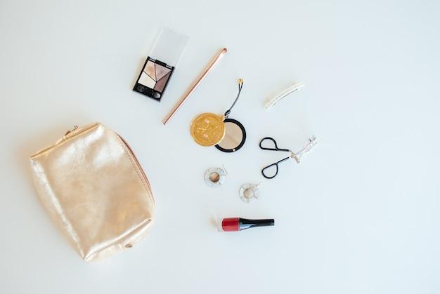 Goldene kosmetiktasche mit kosmetischen schönheitsprodukten auf hellem hintergrund. flach liegen. vorlage für weibliche blog social media.
