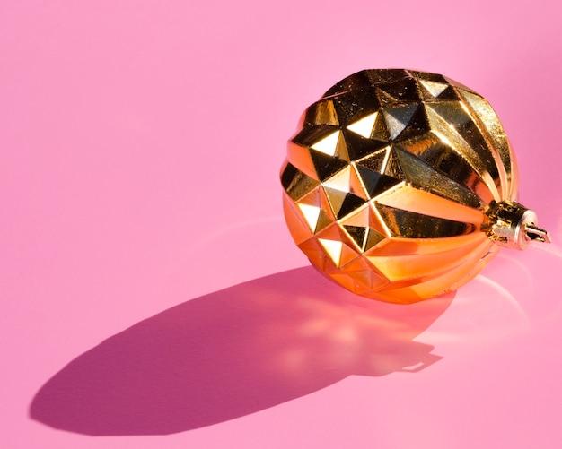 Goldene kugel auf rosa hintergrund