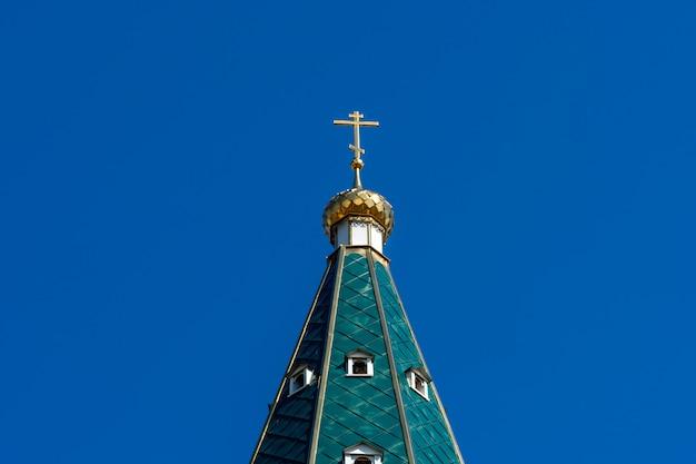 Goldene kuppel mit einem kreuz auf dem grünen dach der russisch-orthodoxen kirche