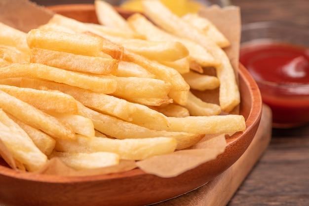 Goldene leckere pommes frites auf kraft-backblechpapier und serviertablett zum essen mit ketchup und gelbem senf, nahaufnahme, lebensstil.