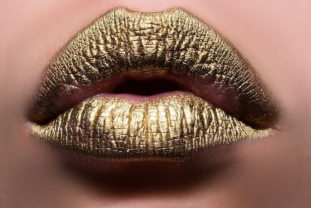 Goldene lippen. frau würde mit goldenem lippenstift auf der lippe hautnah. glitzernde glänzende lippen beißen.