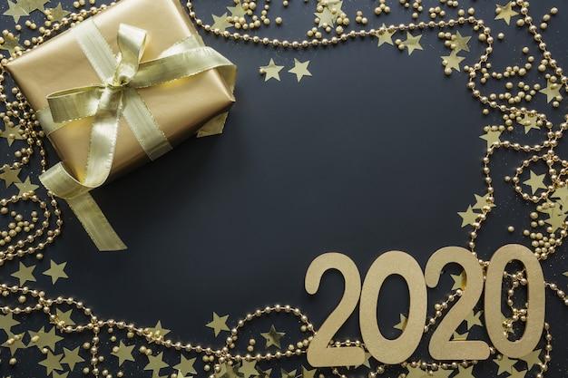 Goldene luxusgeschenkbox mit datum 2020 am schwarzen hintergrund weihnachtsboxen-tagesflachlage weihnachten. neujahr.