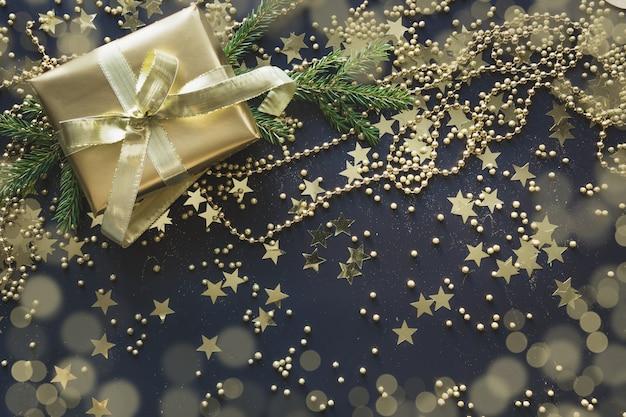 Goldene luxusgeschenkbox mit goldband auf glanzschwarzem. weihnachten. flach liegen. ansicht von oben. festliche kulisse. weihnachtsmuster. .