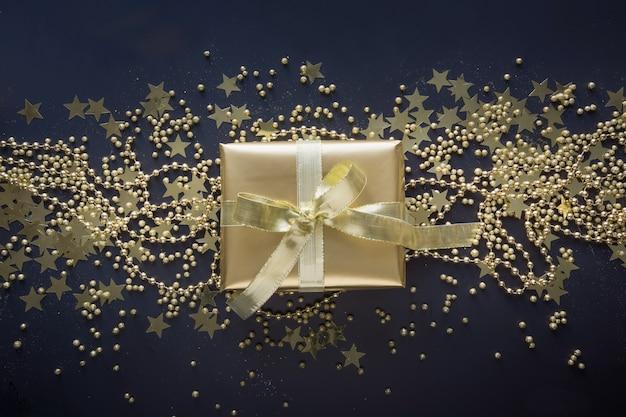 Goldene luxusgeschenkbox mit goldband auf glanzschwarzhintergrund. weihnachten, geburtstagsgeschenk. flach liegen. ansicht von oben. weihnachten