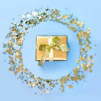 Goldene luxusgeschenkbox um sternkonfettis als kranz auf blau. weihnachtsfeier. flach liegen. sicht von oben. weihnachten.