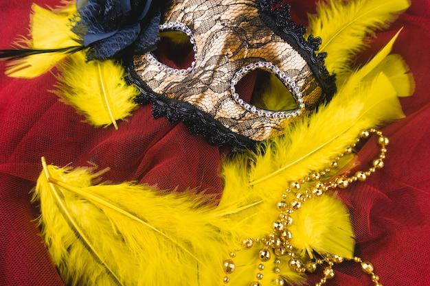 Goldene maske mit gelben federn