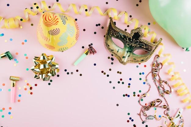 Goldene maskeradekarnevalsmaske mit parteidekorationen auf rosa hintergrund