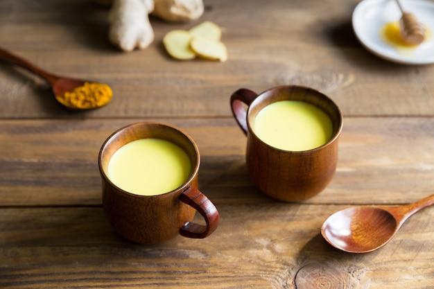 Goldene milch des kräutergesunden indischen getränks mit kurkuma-wurzelpulver in zwei tassen auf hölzernem hintergrund