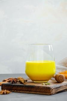 Goldene milch in einem glas auf einem holzbrett mit honig und anderen gewürzen
