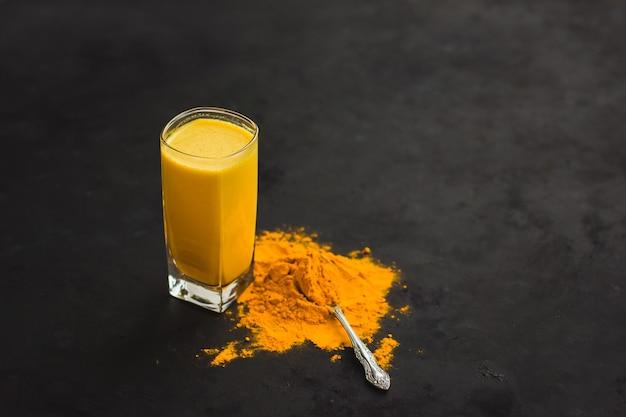 Goldene milch, kurkuma latte, goldene latte auf dunklem hintergrund, gewürze von indien gesundes essen