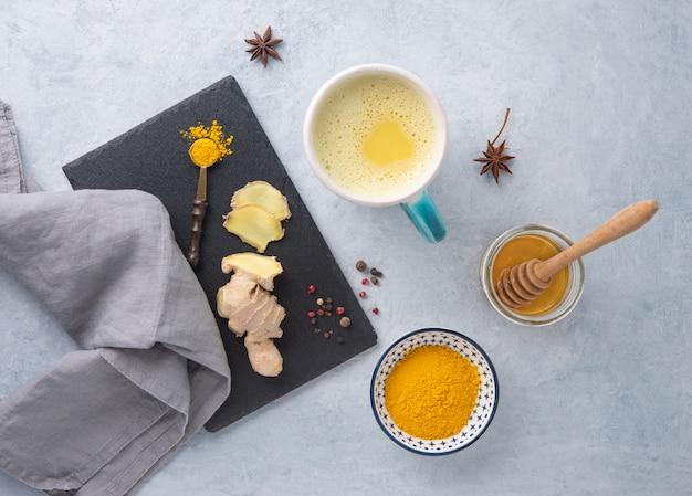 Goldene milch mit kurkuma, gewürzen und honig auf blauem hintergrund