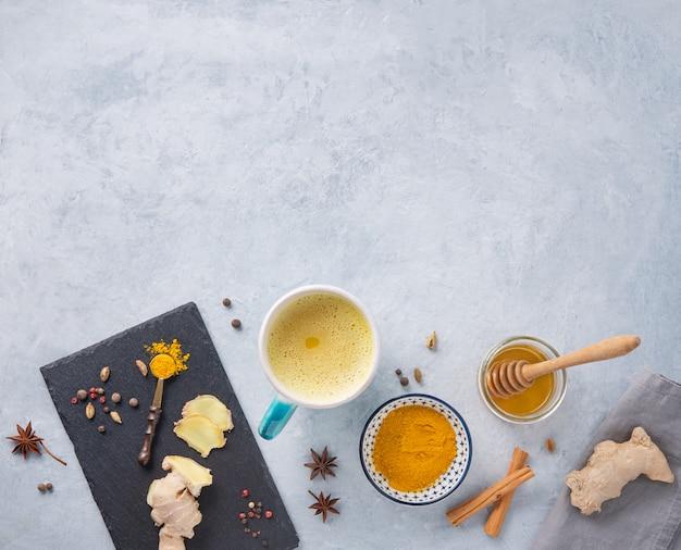 Goldene milch mit kurkuma, gewürzen und honig auf grauem hintergrund