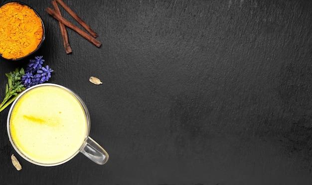 Goldene milch mit kurkuma und anderen gewürzen auf einer schwarzen oberfläche