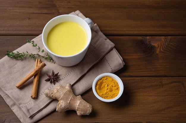 Goldene milch mit kurkuma und zimt. diät, gesund und entgiftungsgetränk. trendiges getränk. draufsicht