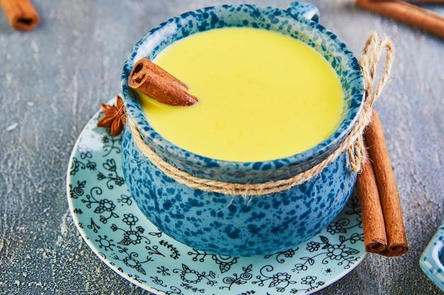 Goldene milch mit kurkuma, zimtstangen, kurkuma und anis auf blauer oberfläche