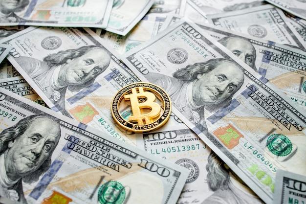 Goldene münze bitcoin auf banknoten von einhundert dollar. tauschen sie bitcoin-bargeld gegen einen dollar. kryptowährung