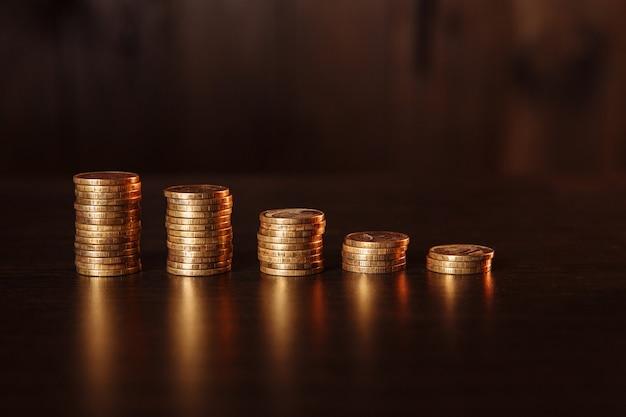 Goldene münzen als grafik in einem holzraum angeordnet.