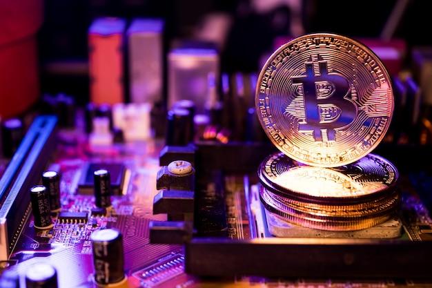 Goldene münzen mit bitcoin-symbol auf einem hauptplatinencomputer.