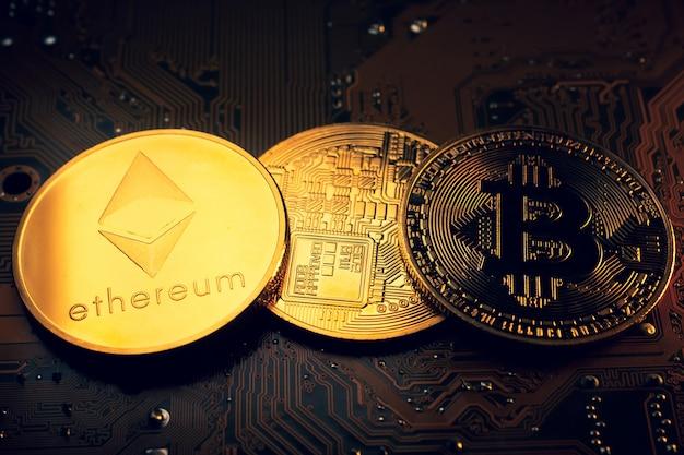 Goldene münzen mit ethereum und bitcoin-symbol auf einem mainboard.