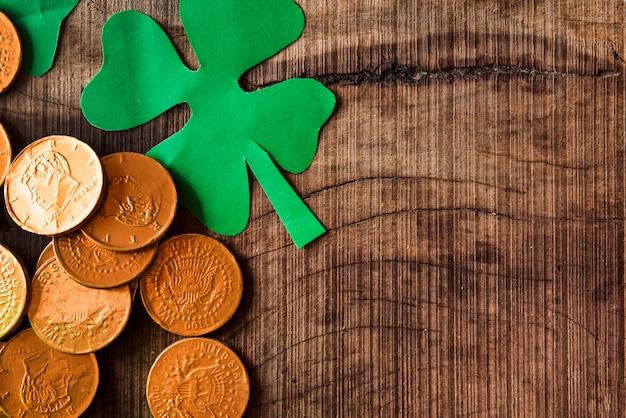 Goldene münzen und papiershamrocks auf holztisch