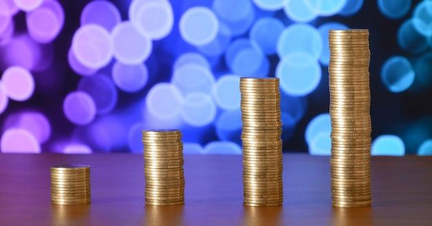 Goldene münzenstapel angeordnet als diagramm. zunehmende spalten von münzen