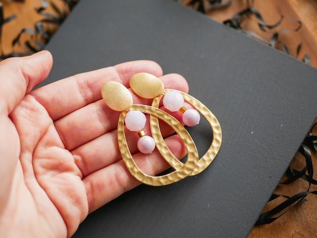 Goldene ohrringe. damenschmuck. weinlesedekorationshintergrund. wunderschöne broschen, armbänder, halsketten und ohrringe in goldtönen auf einem holztablett. flache lage, draufsicht