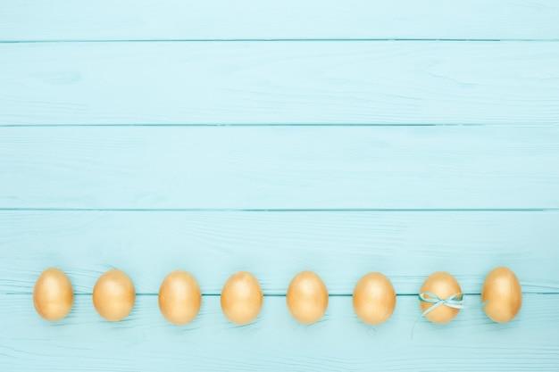 Goldene ostereier auf blauem hölzernem hintergrund. kopierraum, flach liegen.