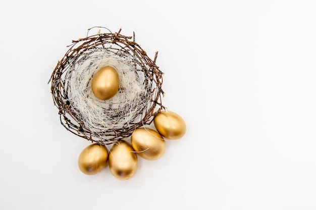 Goldene ostereier in einem kasten mit goldenen sternen auf weißem hintergrund