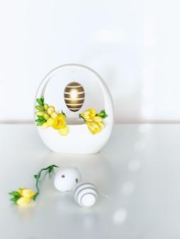 Goldene ostereier mit streifen tupfen und gelber freesienblume, tolles design für jeden zweck.