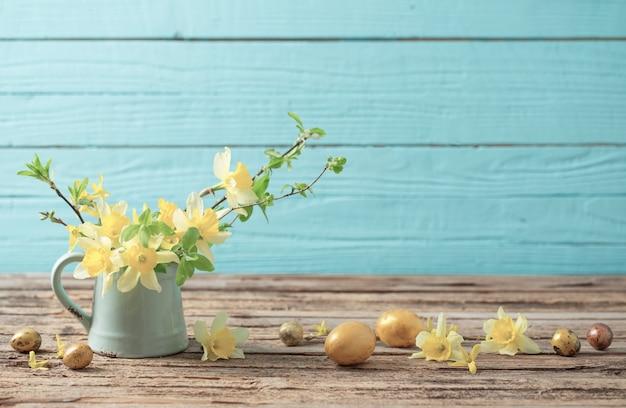 Goldene ostereier und gelbe blumen auf hölzernem hintergrund