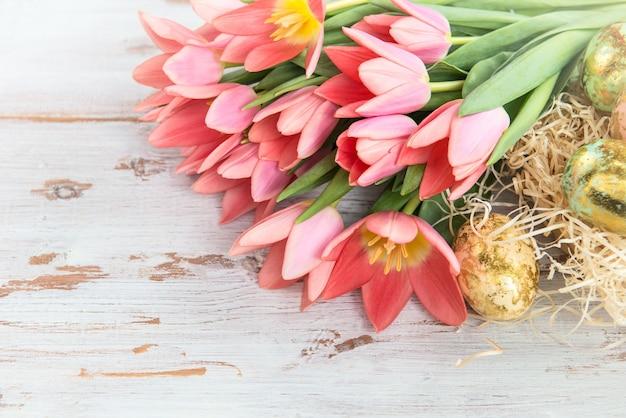 Goldene ostereier und rosa tulpen auf hellem hintergrund