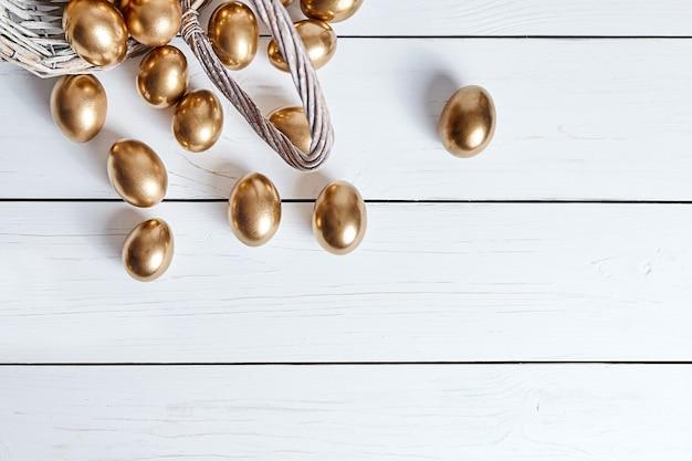 Goldene ostereier verschütteten aus weidenkorb auf weißem holztisch