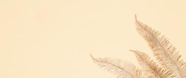 Goldene palmblätter auf beigem papier