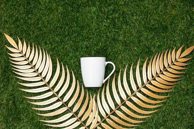 Goldene palmenzweige und tasse auf grünem gras.