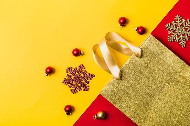 Goldene papiereinkaufstascheschneeflocken und -bälle auf geometrischem hintergrund weihnachtsverkaufskonzept