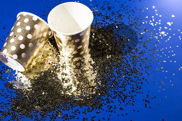 Goldene pappbecher für geburtstagsfeier mit goldenem konfetti auf blauem hintergrund.