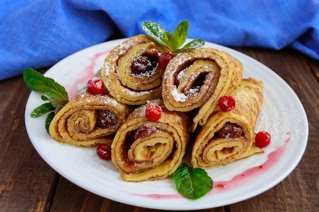 Goldene pfannkuchen in form einer rolle mit erdbeermarmelade und puderzucker auf einem weißen teller auf einem holztisch. nahansicht. frühstück