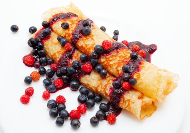 Goldene pfannkuchen mit beerensauce mit blaubeeren und walderdbeeren